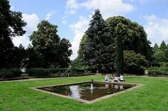 Picknick am Brunnen auf einer Wiese im Winterhuder Stadtpark.