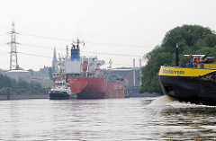 Tankschiff im Harburger Tankhafen - im Vordergrund der Bug eines fahrenden Binnenschiffs auf der Süderelbe.