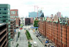 Moderne Architektur und historische Lagergebäude in der Hamburger Hafencity - Blick in die Strasse Am Sandtorkai - im Hintergrund die Baustelle der Elbphilharmonie.