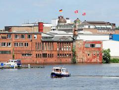 Altes Industriegebäude am Ufer der Bille in Hamburg Hammerbrook; im Hintergrund Fahnen auf dem Dach vom Störtebeker Haus.