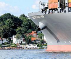 Bug des Containerschiffs MSC FAUSTINA auf der Elbe - im Hintergrund die Strandperle am Elbstrand von Hamburg.