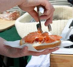 Biohof Gut Wulksfelde - Bauernmarkt. Eine Scheibe Brot wird mit Lachs belegt.