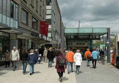 Eingang zur U- und S Bahnstation am Jungfernstieg - Moderner Eingang zu Hamburgs Untergrundbahn. Kaufhäuser an der Hamburger Geschäftsstrasse.