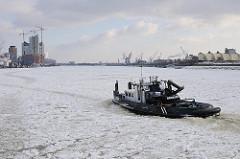 Hamburg im Winter - Eis auf der Elbe - Schubschiff zwischen Eisschollen - im Hintergrund die Baustelle der Albphilharmonie.