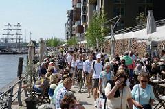 Aussengastronomie in der Sonne in der Hafencity - die Gäste sitzen am Dalmannkai und blicken aufs Wasser.