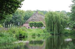 Marmstorfer Feuerlöschteich - Reetdach eines Bauernhauses im Hintergrund - Weiden mit ins Wasser hängenden Zweigen am Ufer des Dorfteiches.