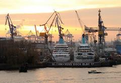 Kreuzfahrtschiffe im Dock der Werft Blohm + Voss im Hamburger Hafen; Hafenkräne im Sonnenuntergang.