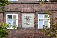 """Inschrift in der Hausfassade  - """"IN DER WELT EIN HAUS - IM HAUS EINE WELT - UND WELT UND HAUS IN GNÄDIGER HAND"""" Fotos aus Hamburg Dulsberg."""