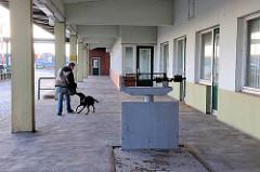 Rampe der stillgelegten Zollstation Reiherstieg Hauptdeich - Fussgängerin mit Hund in Hamburg Wilhelmsburg.