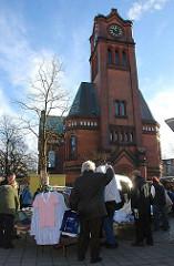 Wochenmarkt an der Apostelkirche - Stand mit Kleidung und Hemden.