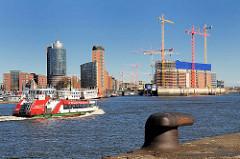 Bürogebäude am Kehrwieder - Baustelle der Elbphilharmonie (2009); eine Hafenfähre fährt zum Anleger Theater am Hafen - im Vordergrund ein Eisenpoller zum Vertauen von Schiffen.