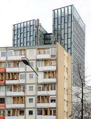 Wegen Einsturzgefahr geräumtes Essohaus auf Hamburg St. Pauli - die Balkons sind mit Holzbalken gegen den Absturz gesichert - im Hintergrund die moderne Architektur der Hochhäuser Tanzende Türme der Hamburger Architekten Bothe, Richter, Teherani.
