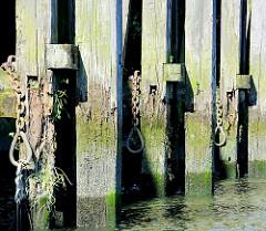 Alte, angefressene Holzdalben / Streichdalben mit Eisenketten - Relikte / Überbleibsel vom alten Hamburger Hafen.