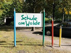 Schild Schule am Wald - grosse Buntstifte.
