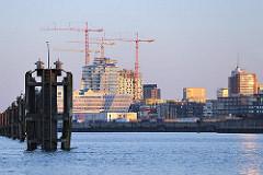 Sonnenaufgang in Hamburg - Morgensonne auf die entstehende Hafencity - Baukräne an der Baustelle der Elbphilharmonie.