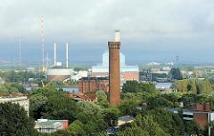 Der 64m hohe Wasserturm wurde 1848 von Alexis de Chateauneuf errichtet und steht unter Denkmalschutz - direkt hinter dem Turm Speichergebäude am Ufer der Billwerder Bucht sowie die hohen Gebäude des Kraftwerks Tiefstack in Hamburg Billbrook.