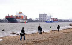 SpaziergänerInnen am Strand bei Hamburg Oevelgönne  - Schiffsverkehr auf der Elbe.