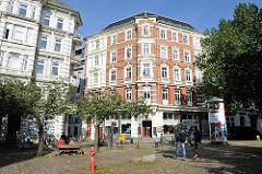 Etagenhäuser im Architekturstil der Gründerzeit an der Trommelstrasse in Hamburg St. Pauli. Passanten auf dem Hein Kölisch Platz.