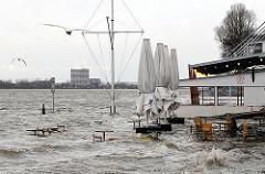 Strandkiosk und Stranperle werden vom Hochwasser erreicht - Tische und Stühle stehen unter Wasser - Hochwasserwarnung in Hamburg.