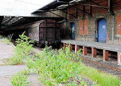 Ehem. Güterbahnhof Oberhafen - junge Birken wachsen auf dem Bahnsteig - Güterwaggons vor dem Klinkerlagergebäude in der Hafencity Hamburg.