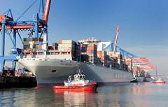 Der Containerfrachter NYK HELIOS am Containerterminal Hamburg Altenwerder; Schlepper unterstützen das Schiff beim Ablegen und Auslaufen aus dem Hamburger Hafen. Das 2013 gebaute Containerschiff hat eine Länge von 365,50m und eine Breite von 48,40m; d