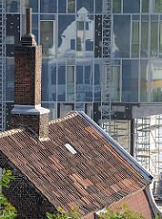 Historisches Ziegeldach, hoher Schornstein spiegelt sich in der Glasfassade eines Bürohochhauses an der Grossen Elbstrasse.