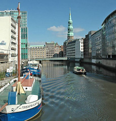 Schiffe auf dem Hamburger Nikolaifleet - ein Fahrgastschiff der Fleetrundfahrt fährt Richtung Trostbrücke - im Hintergrund der Kirchturm der St. Katharinenkirche.