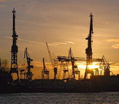 Sonnenuntergang über Hamburg Steinwerder - Werftkräne der Werft Blohm + Voss im Abendlicht.