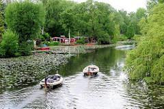 Wilhelmsburger Dove Elbe - Wochenendhäuser am Ufer, zwei Tuckerboote / Motorboote  in Fahrt. Mit Bäumen, Weiden dicht bewachsenes Flussufer.