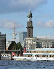 Wahrzeichen von Hamburg - Blick über die Elbe zum Michel und Telemichel. Schiffsbug mit Hamburgflagge.
