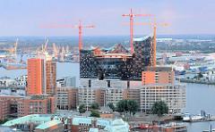 Blick auf die Baustelle der Hamburger Elbphilharmonie und der Büroturm am Kehrwieder - Kehrwiederspitze - am anderen Elbufer Hafenanlagen auf dem Kleinen Grasbrook - Fotos aus der Hansestadt Hamburg - Bilder aus dem Stadtteil Hafencity.