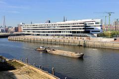 Blick vom Petersenkai des Baakenhafens zum Versmannkai / Buenos Aires Kai - Neubau der Hafencity Universität; ein Schubschiff bringt eine Schute zur Baustelle im Hafenbecken.