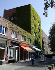 Hamburg Winterhude - Geschäfte und Wohnhäuser in der Jarrestadt - Hausfassade mit Wein bewachsen.