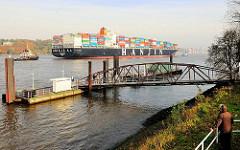 Fähranleger Bubendeyufer in Hamburg Waltershof - ein Containerschiff läuft mit Hilfe von Schleppern in den Hamburger Hafen ein.