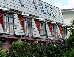 Fenstergauben an einem Hausdach - blühende Blumen und Sträucher im Vorgarten des Gebäude.