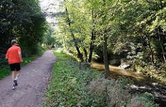Jogger auf dem Wanderweg an der Berner Au / Stadtteil Farmsen Berne.