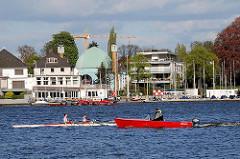 Ruderboot mit Begleitboot auf der Aussenalster vor Hamburg Uhlenhorst. Im Hintergrund die Kuppel und Minarette der Imam-Ali-Moschee.