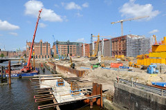 Bauarbeiten am Ufer des Magedburger Hafens in der Hamburger Hafencity - ein Kran auf einem Arbeitponton erledigt Rammarbeiten. Im Hintergrund des Gebäude des  Kaispeichers B, in dem das Maritime Museum seine Ausstellungsräume hat.