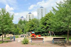 Kinderspielplatz im Grünen Zentrum von Hamburg - Lohbrügge - Hochhäuser der Grosssiedlung im Hintergrund.
