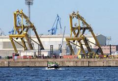 Sprengung von Hafenkränen in Hamburg Steinwerder - die hohen Stahlgerüste stürzen auf die Kaifläche - ein Barkasse fährt im Ellerholzhafen.