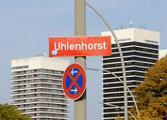 Stadtteilschild UHLENHORST an einem Laternenpfahl - Stadtteilgrenze; im Hintergrund Hochhäuser am Mundsburg.