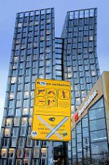 Schild Waffen verboten - Hamburg St. Pauli, Reeperbahn - Videoüberwachung durchgestrichen - im Hintergrund das Operettenhaus und die Doppeltürme Hochhaus Tanzende Türme.