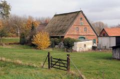 Bauernhof mit Strohdachhaus und Scheune  / Wiese mit Gatter.