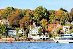 Blick zur Strandperle am Ufer der Elbe in Hamburg Othmarschen - herbstliche gefärbte Bäume am Elbhang.