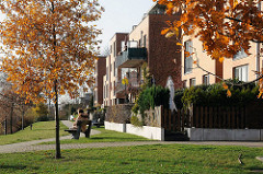 Neubauten am Billeufer - Herbstbaum mit Blättern - Frau auf Parkbank.