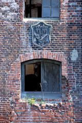 Ziegelfassade der Harburger Mühlenbetriebe - Grünpflanzen wachsen aus dem historischen Gemäuer. Eisenplakette mit Anker, Buchstaben und römischne Ziffern. (2007)