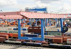 Güterbahnhof auf dem Gelände des Container Terminals Altenwerder - mit Containern beladene Güterwagen stehen unter dem Portalkan.