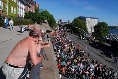 Demonstration auf der Hafenstrasse bei den St. Pauli Landungsbrücken - Biertrinkende Zuschauer oberhalb der Strasse.