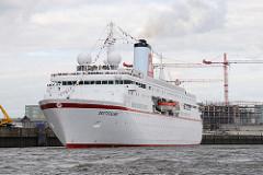 Das Kreuzfahrtschiff DEUTSCHLAND legt ab; im Hintergrund eine Baustelle am Baakenhafen der Hamburger Hafencity.