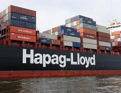 Schriftzug der Hapag-Lloyd an der Bordwand eines Containerschiffs im Hamburger Hafen.